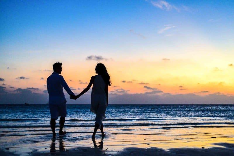 par hålla händer och gå på stranden