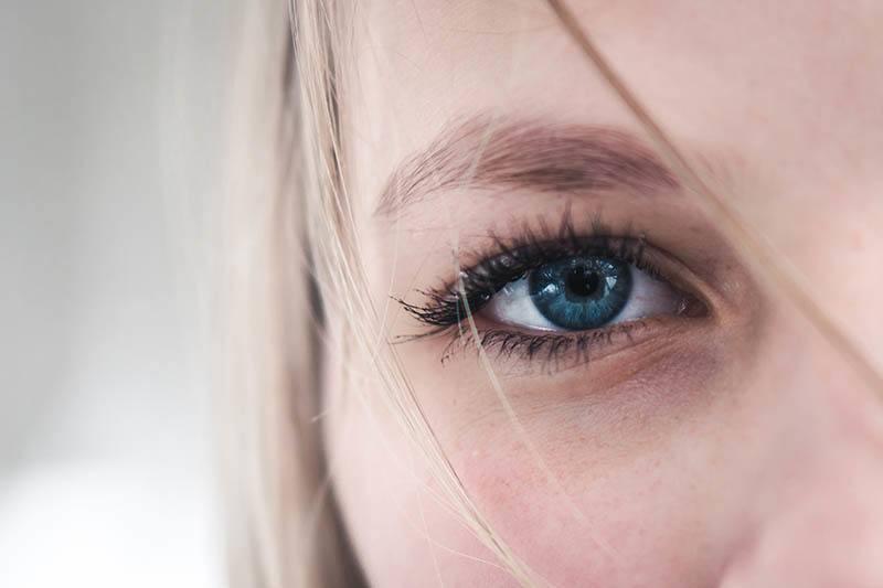 närbildfoto av kvinnans blåa öga