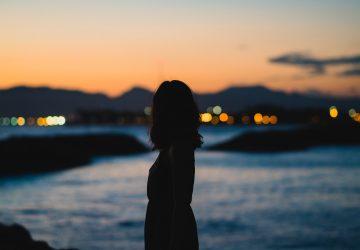 kvinna som står vid vattnet