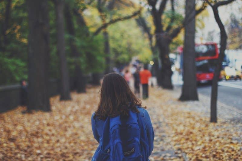 kvinna med ryggsäck som går på gatan