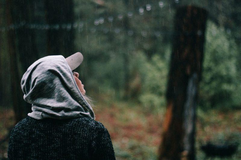 kvinna i skogen på regnet