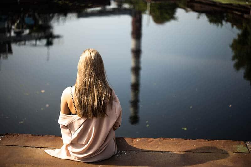 kvinna sitter vid sjön
