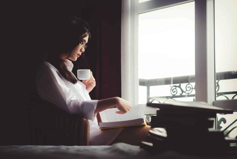 kvinna som sitter vid fönstret