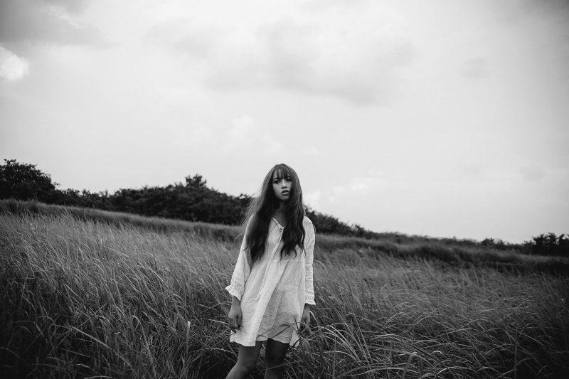 kvinna i vit klänning som står i naturen