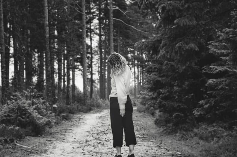 kvinna som står ensam i skogen