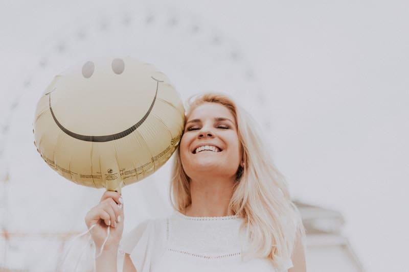kvinna med en smiley ballong