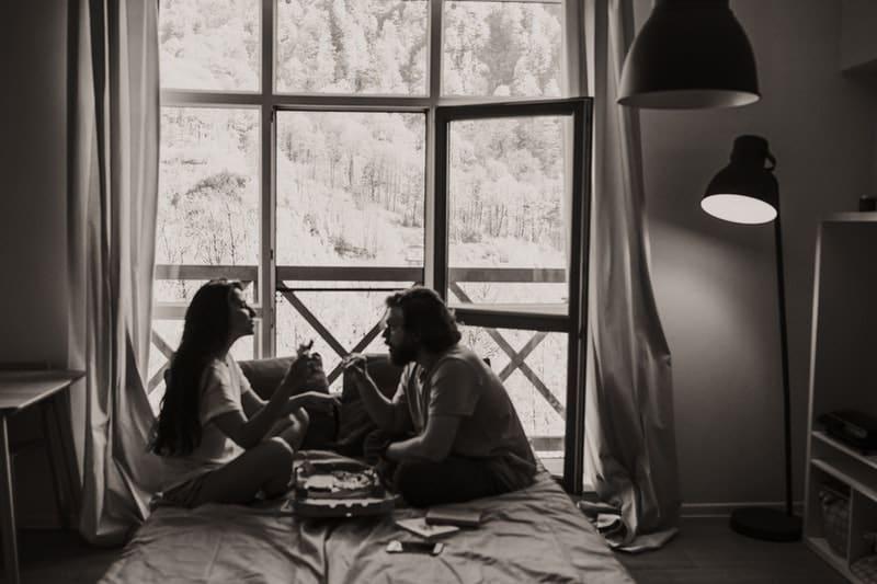 man och kvinna som sitter på sängen och pratar