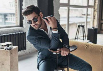 män som bär kostym och solglasögon som poserar hemma