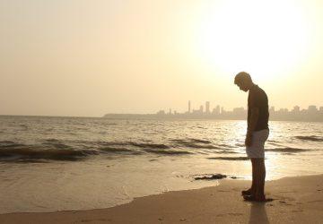 man med dålig hållning tittar på havet