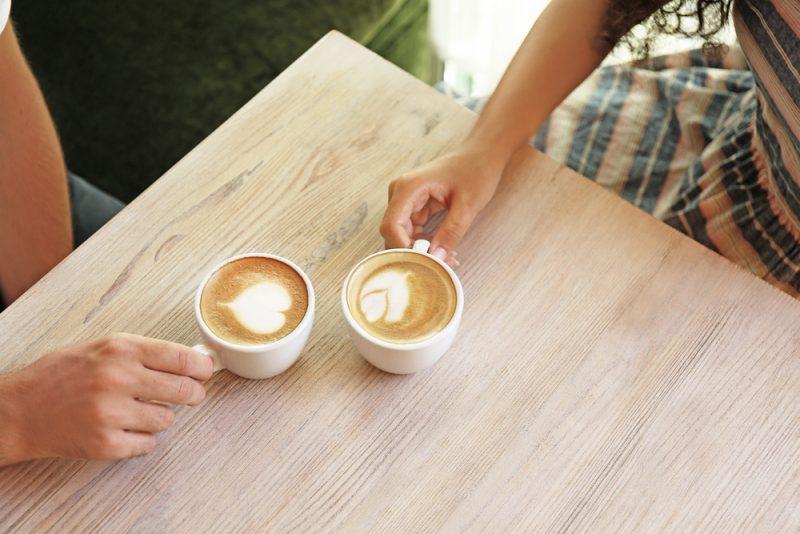 Händer som håller koppar kaffe