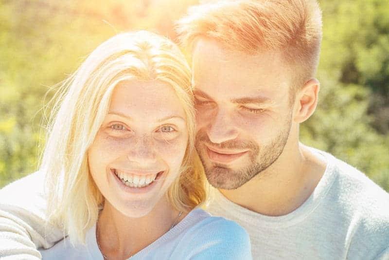 närbildfoto av leende par som kramar under dagen