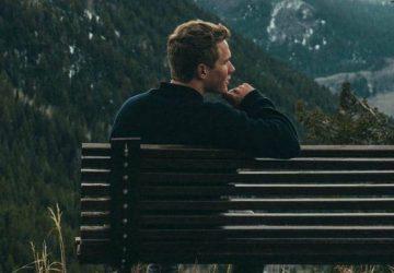 man sitter ensam på bänken
