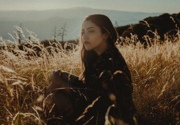 kvinna sitter på ett vetefält