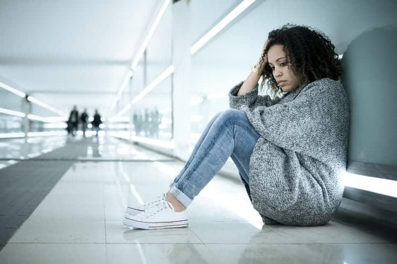 ledsen kvinna lutad mot en vägg