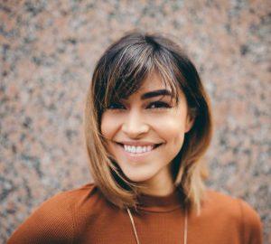 kvinna med brunt hår i brun skjorta ler nära brun vägg
