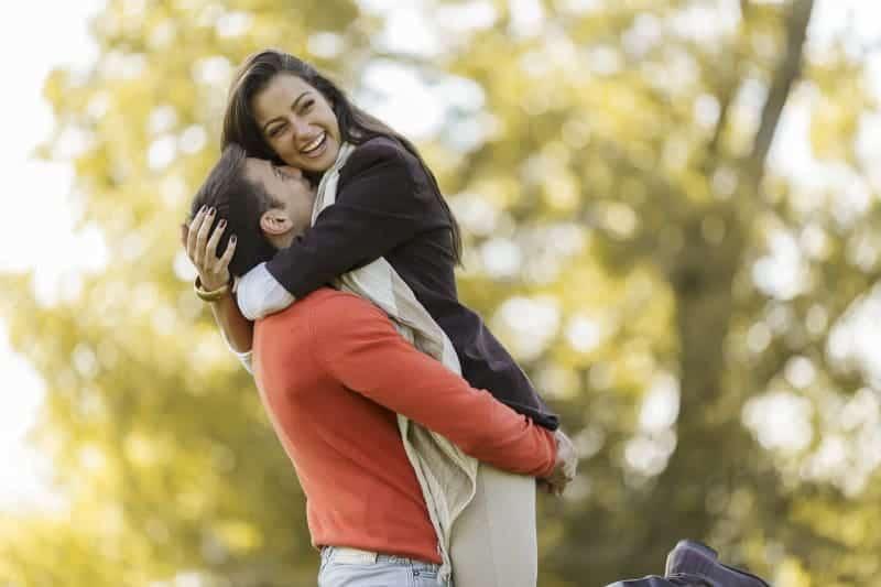en man bär en glad kvinna