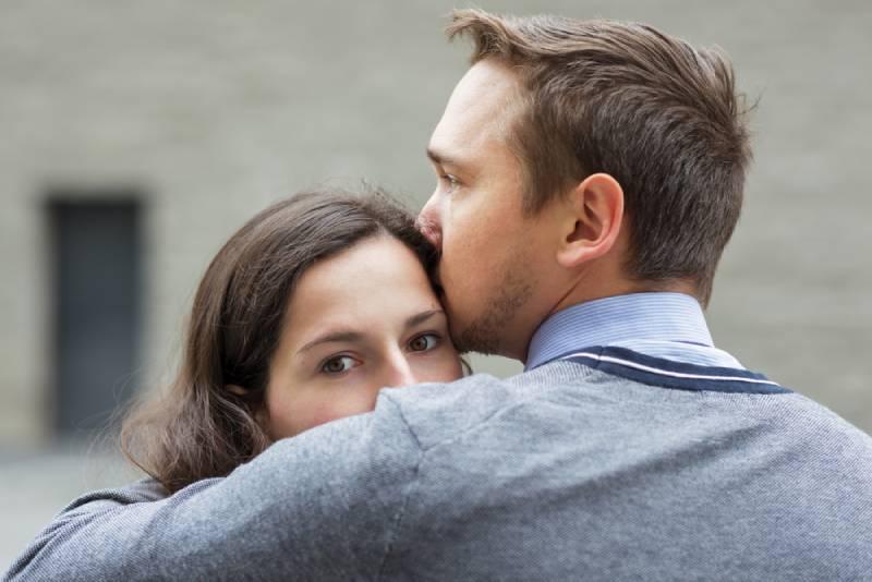 en man kysser en kvinna i pannan