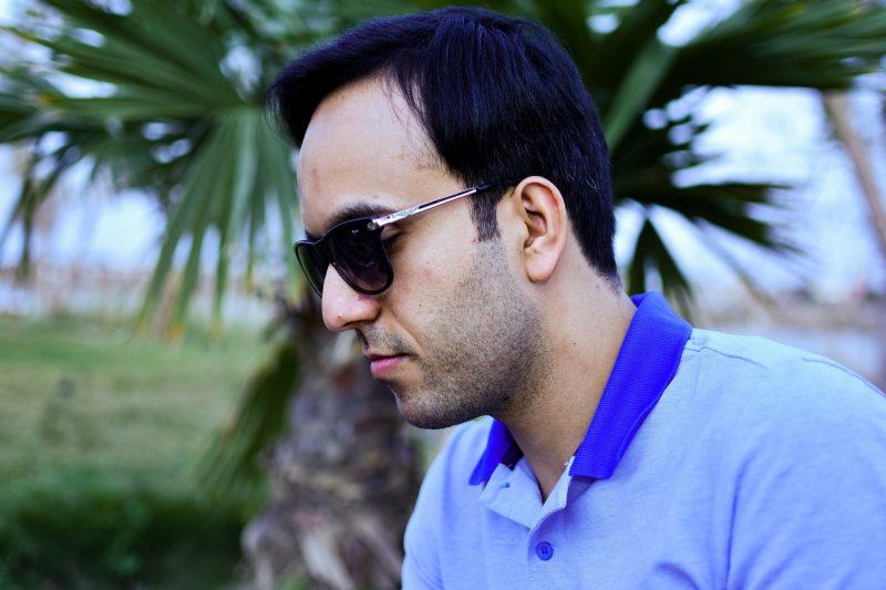 man som bär solglasögon i blå skjorta
