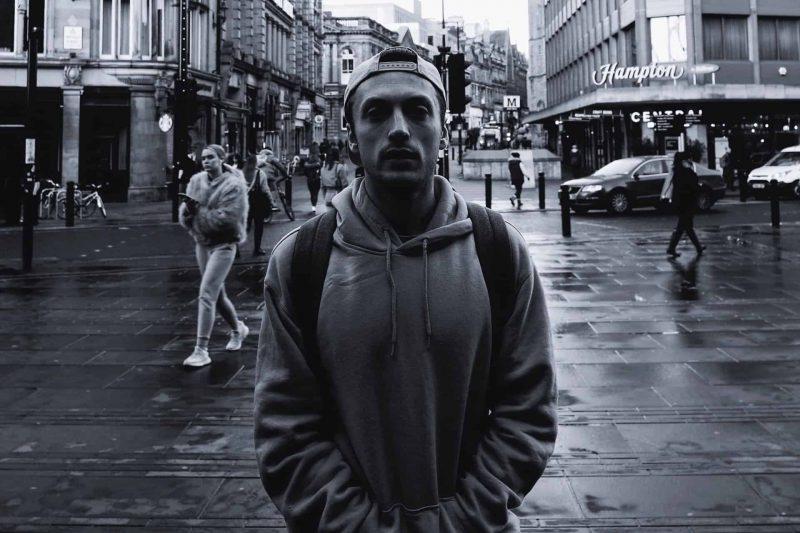man som står på vägen som bär grå tröja