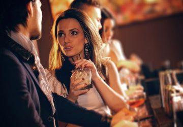 man och kvinna pratar i en bar