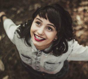 en lycklig kvinna står med öppna armar och ser på himlen