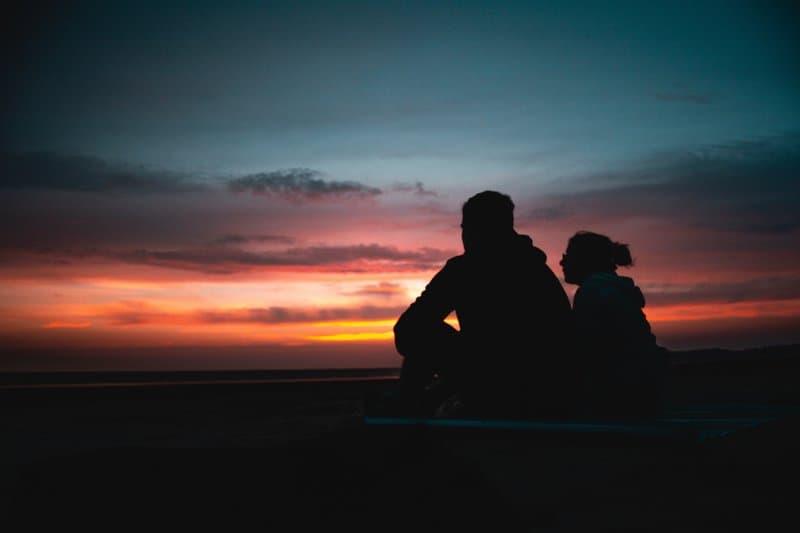 ett älskande par som sitter på stranden och tittar på solnedgången