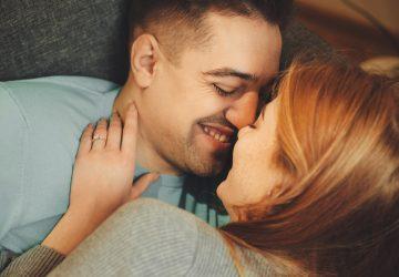 par som ligger i sängen och kramar och ler