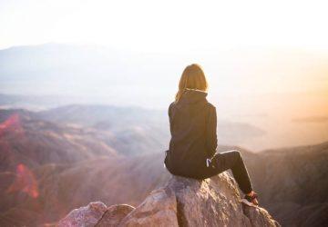 en kvinna sitter på en sten