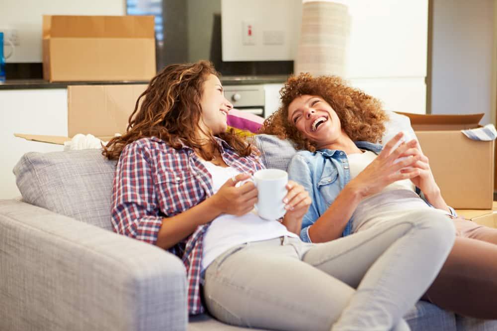 två kvinnor som sitter på sängen och ler