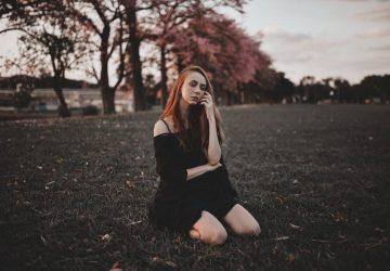 kvinna sitter på gräset