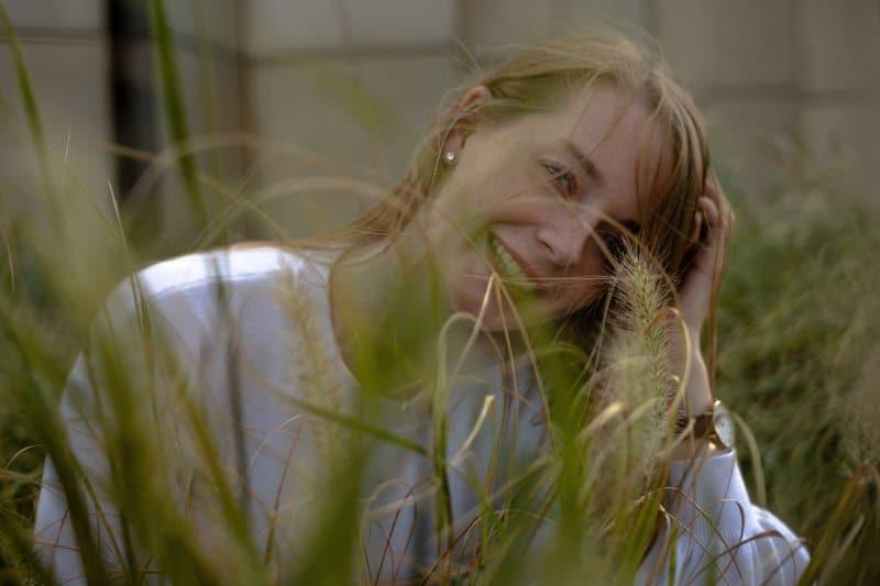 en kvinna i en vit tröja sitter i ett vetefält