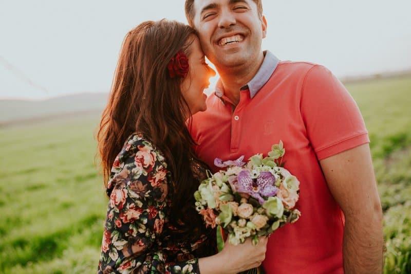 en leende flicka med blommor i handen kramar en leende kille