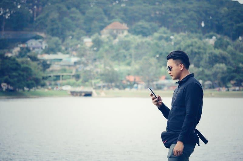 en man i en svart skjorta använder en mobiltelefon