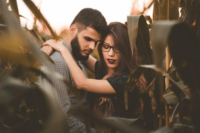 en man med skägg och en tjej med glasögon står omfamna i ett sädesfält