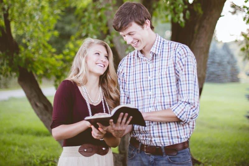 en man och en kvinna läser en bok i parken