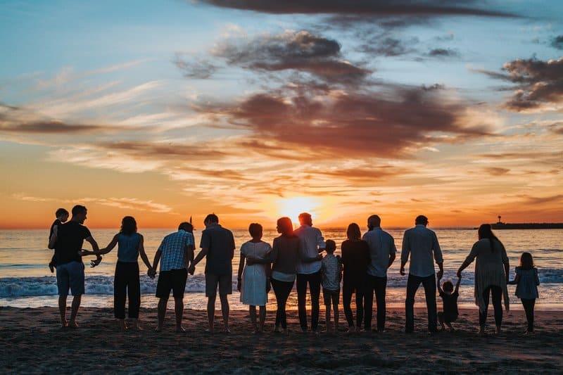 en stor familj på stranden och tittar på solnedgången