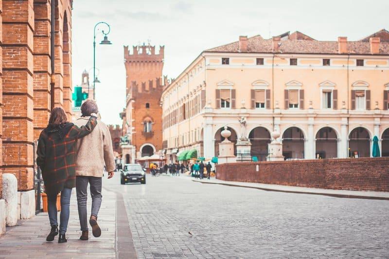 en tjej i en rutig kappa kramar killen som hon går med