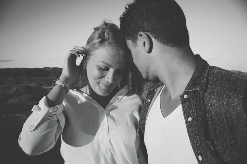 en tjej med ett leende i ansiktet i armarna på en kille i en texaskjorta
