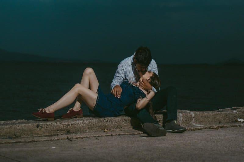 kvinnan ligger och kysser i mannens knä