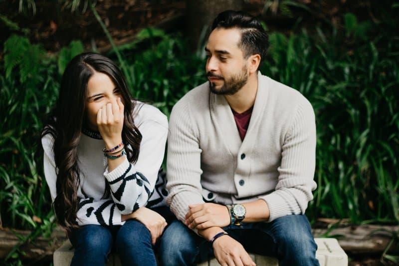 kvinnan skrattar när hon sitter med mannen på bänken