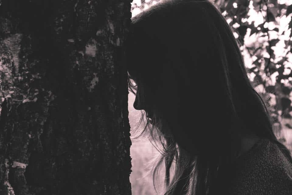 ledsen kvinna med huvudet på trädet