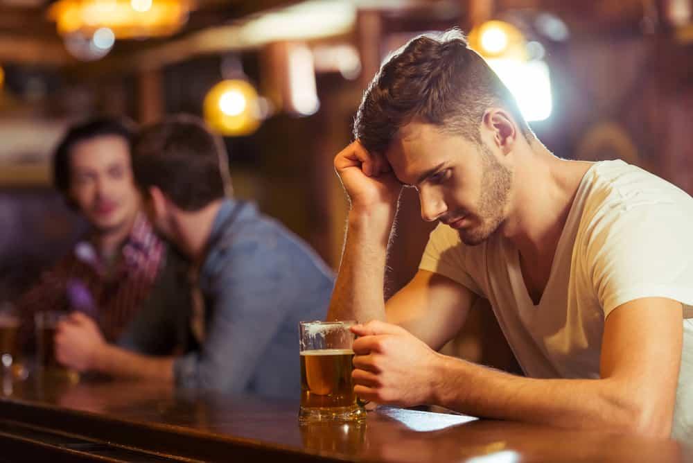 ledsen man som dricker öl i baren