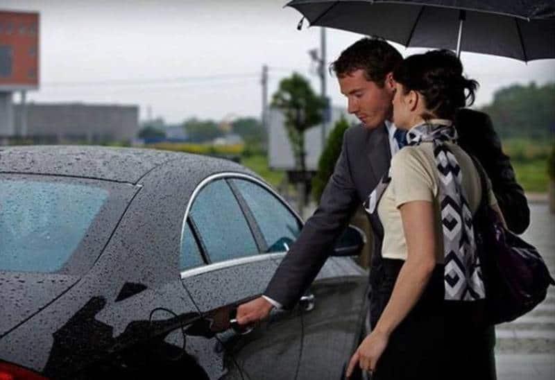 man öppnar en bildörr för woman