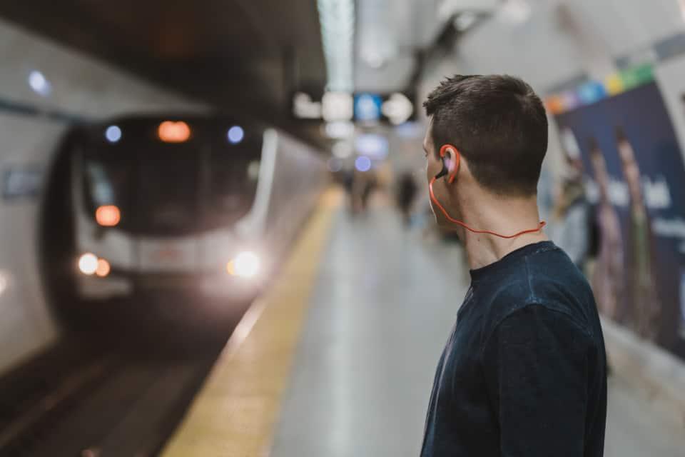 man lyssnar på musik i tågstationen