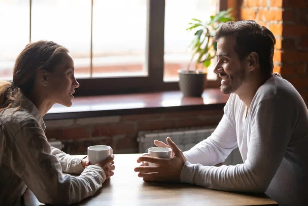 man och kvinna dricker kaffe och pratar