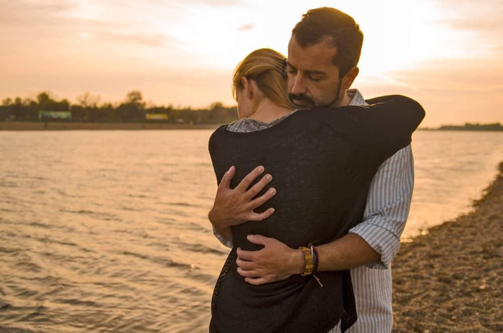 man och kvinna som kramar vid sjön
