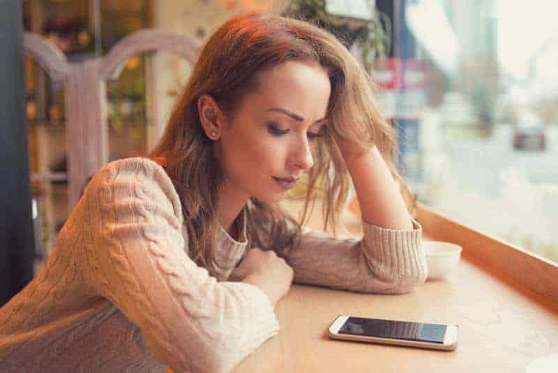 orolig kvinna som tittar på sin telefon på caféet