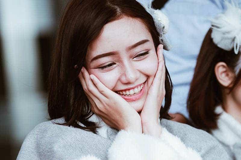 söt leende flicka med händerna i ansiktet