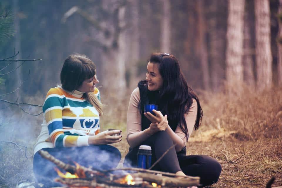 två kvinnor tycker om att campa