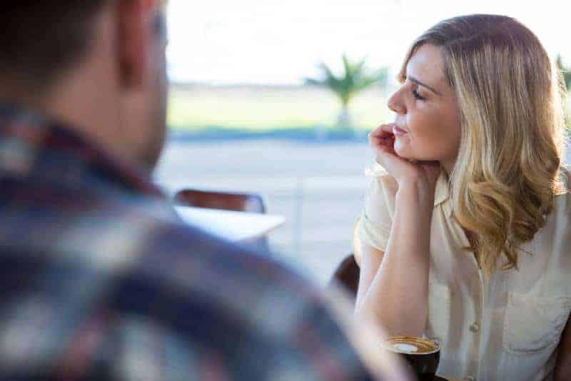 upprörd kvinna som tittar bort medan man sitter med mannen